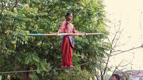 Nandgeon, India - 20180225 - Girl Crosses Slackroap to Entertain Passing Crowd Live Action