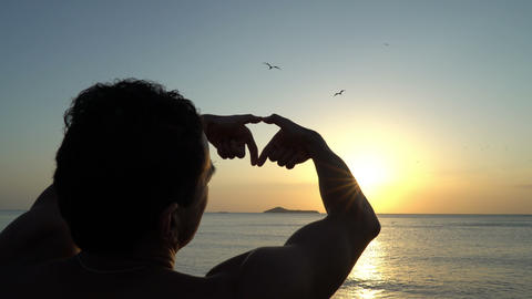 Young man with curly hair making heart with his hands at amazing sunset on the Footage