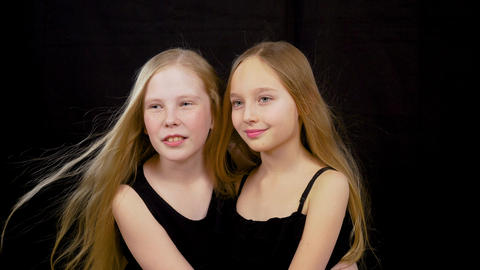 Portrait of beautiful young girls standing isolated cut at black dark background Footage