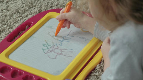 A little girl with red wavy hair lies on the floor and draws on a magnetic board Live Action