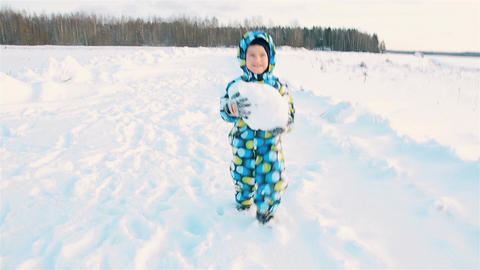 A boy in a colored jumpsuit smiling carries a big snowball Footage