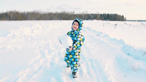 A boy in a colored jumpsuit smiling carries a big snowball Stock Video Footage