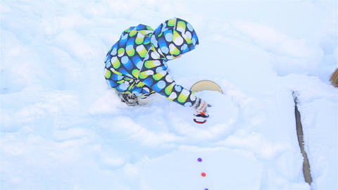 A little boy tries to take out a slippery nose from a snowman Footage