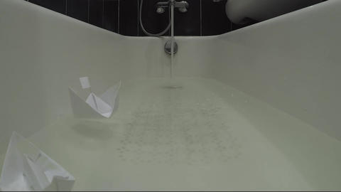 Time laps, bath is filled with water in which 3 paper boats float, the camera is Archivo