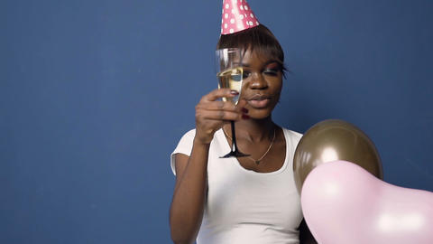 African girl in hat with balloons in the hand clinking glass to camera on the Live Action