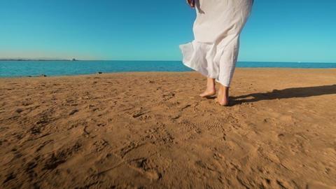 Legs of caucasian girl wearing white long dress walking barefoot sand on sea Footage