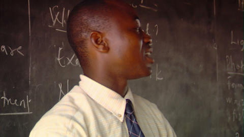 Teacher writing on a blackboard in Africa Footage
