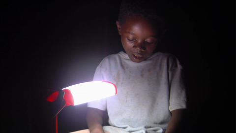 African boy reading by a lamp Live Action