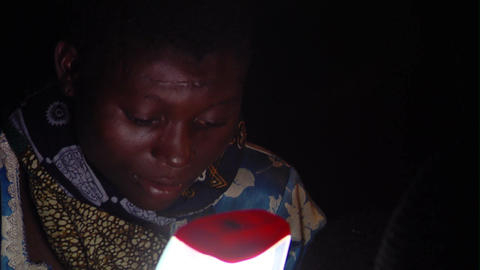 African woman reading in the dark Live Action