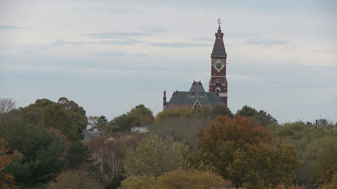 Clock tower of Abbot Hall over autumn treetops in Marblehead Footage