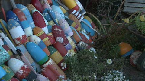 Pan across stacked striped fishing buoys in Massachusetts Live Action