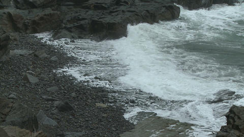 Waves breaking into foam on a rocky beach in Maine Footage