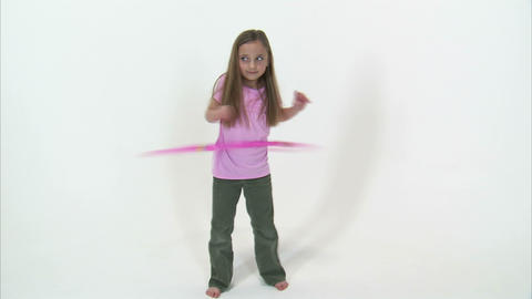 Royalty Free Stock Footage of Young girl doing the hula hoop on a white backgrou Footage