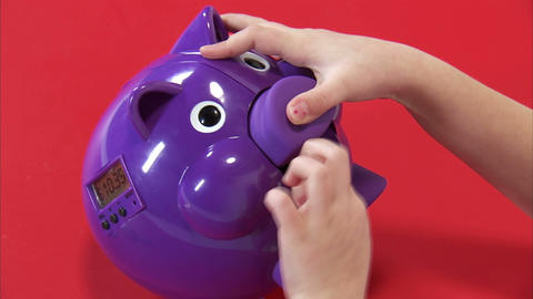 Royalty Free Stock Footage of Young girl putting money in a purple piggy bank Footage