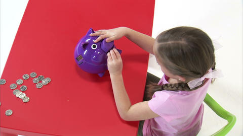 Royalty Free Stock Footage of Young girl putting coins in a purple piggy bank Footage