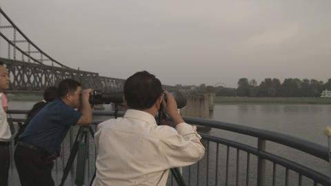 Men viewing North Korea from China Footage