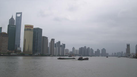 Barges turn with Huangpu River against a background of skyscrapers Footage