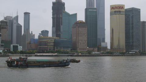 Barges travel down Huangpu River against a background of skyscrapers Footage