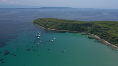 Aerial - Luxury yachts and sailboats anchored in turquoise colored bay Footage
