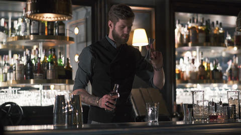 Hipster bartender mixologist combining ingredients and making a whiskey cocktail Live Action