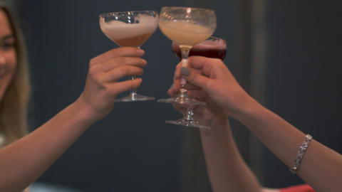 Three women hands clink glasses with cocktails close up. Girls have celebration Live Action