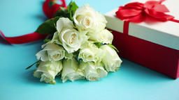 Bouquet of white roses with red bow on blue background. Boxed gift on side Footage