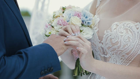 The bride puts the wedding ring on finger of the groom. marriage hands with Footage