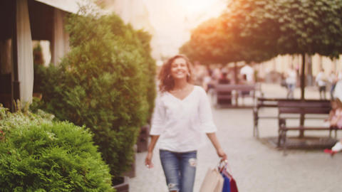 After day shopping. Young woman carrying shopping bags while walking along the Footage