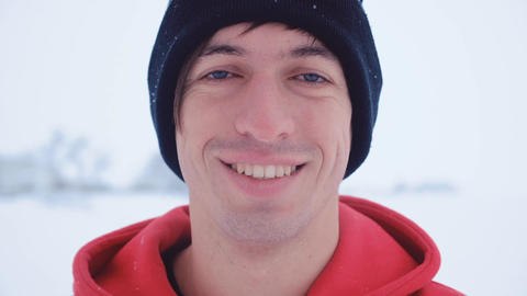 Close-up of the attractive young man look camera smiling in winter snowy cold Live Action