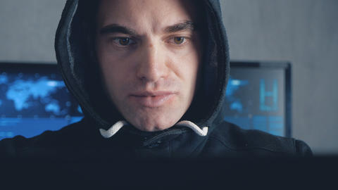 Handsome Male hacker in hood working on a computer in data center Live Action
