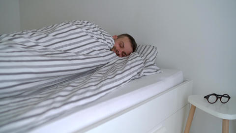 Bearded man waking up in bed under blanket, smiling, putting his eyeglasses on Live Action