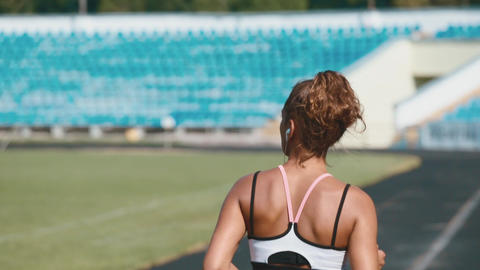 Portrait of a strong fit girl in sportswear running in the stadium. Beautiful Footage