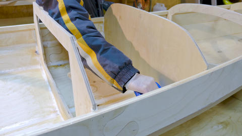 Male hands closeup. He handles the seams of the boat with epoxy glue for GIF
