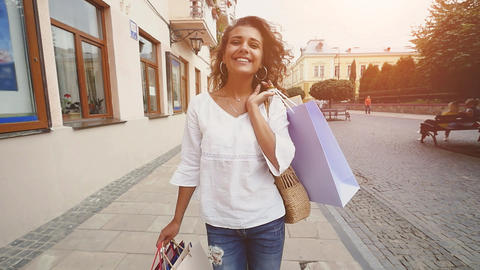 Sale, consumerism: Confident lady with shopping bags walking after shopping time Footage