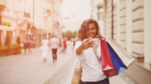 Sale, consumerism: Confident lady with shopping bags make selfie on smartphone Footage