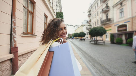 Back view of young woman with shopping bags enjoying in shopping, girl are Footage