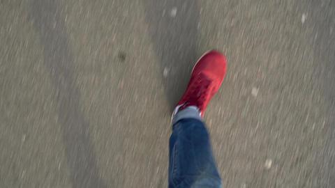 Top view of men's legs in red sneakers walking on asphalt Footage
