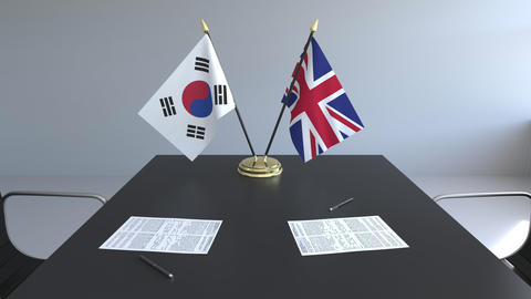 Flags of South Korea and Great Britain and papers on the table. Negotiations and Live Action