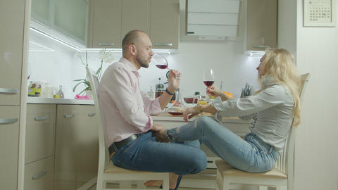 Happy couple toasting with red wine in kitchen ビデオ