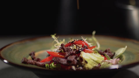 Sesame seeds falling into the plate with the ingredients of fresh salad. Close Live Action