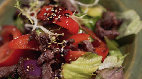 Salad ingredients are in the plate close up. Healthy food with sesame on the top Live Action