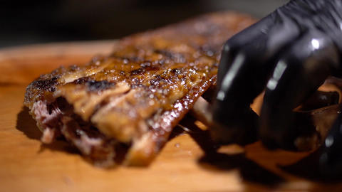 Chef pulls out the bones from just cooked juicy fragrant fried ribs on the Live Action