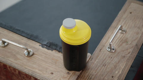 Sportswoman take bottle with sports nutrition and putit on bench. Close up with GIF