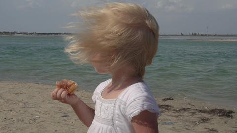 Little girl has breakfast on the beach. A child on the coast. Happy joyful child Live Action