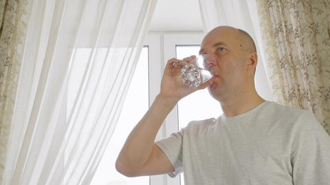Adult bald man drinking water from glass on window background on home kitchen GIF