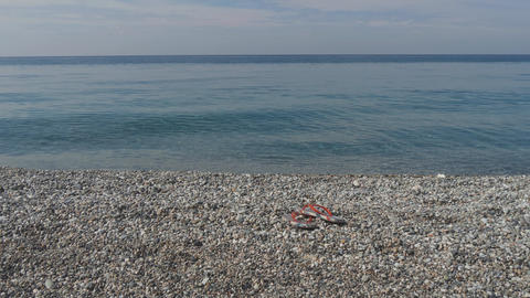 Smooth pebbles in clear azure sea waves. Pair of flip-flops on a seashore. Slow GIF