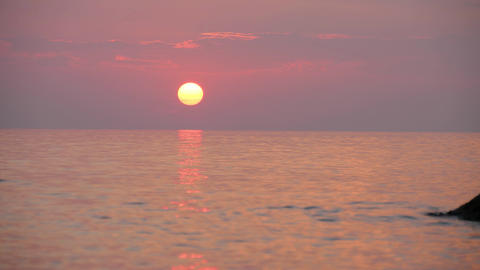 Big disk of the sun in cloudy pink sky. Sunset over sea. Water reflects sunlight ビデオ