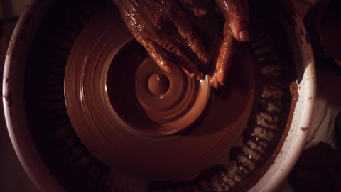 Brown clay plate is slowly getting shaped by hands on rotating potter's wheel Live Action