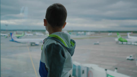 Baby boy in airport waits for departure and looks on support vehicles through Live Action