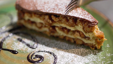 Close-up of a piece of delicious cake lying on a plate. A fork cuts a piece of Live Action
